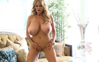 Kelly isn't wearing much to begin with but takes it off to get at her huge tits.