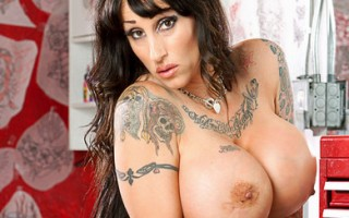 Tattooed chick with huge boobs fucks in a tattoo parlor.